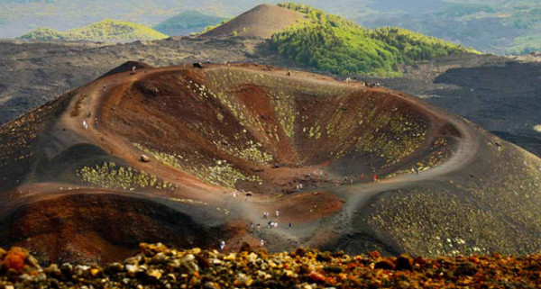 Tourists explore a volcanic crater on Mount Etna